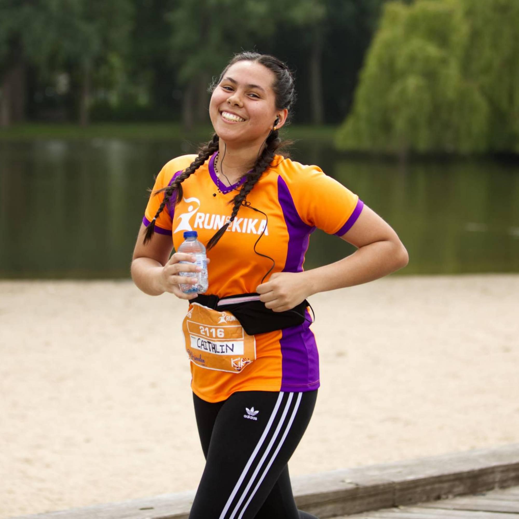 Meisje met Run for KiKa shirt loopt met waterflesje in hand, water op de achtergrond.