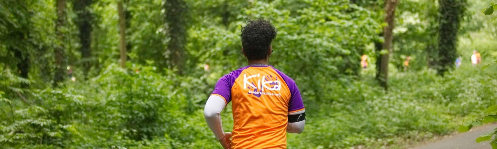 Man met Run for KiKa shirt aan, met de rug naar je toe, rent door een bos.