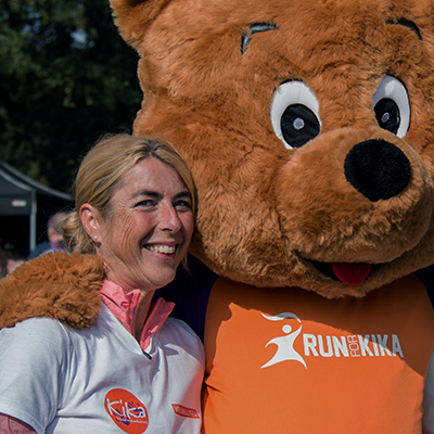 A volunteer at the Run for KiKa Winterrun hugs the KiKa bear after a day of charity work.
