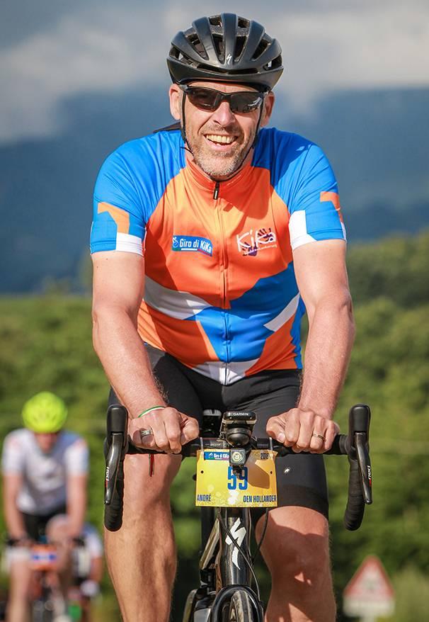Blije wielrenner op de fiets in zijn Giro di KiKa wielershirt.