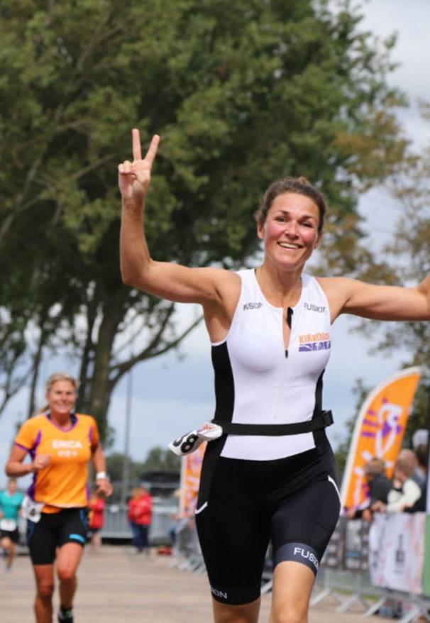 Blije KiKathleet komt met een peaceteken in een trisuit over de finish