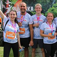 Runners van bedrijventeam Peek & Cloppenburg poseren met hun medaille na de finish van Run for KiKa. Ze vertellen hoe het is om als bedrijf mee te doen aan dit sportevenement voor KiKa.