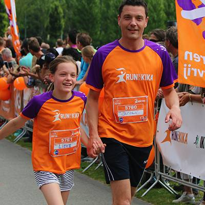 Mother and son are running for children with cancer and happily pass the finish line of the Run for KiKa Winterrun in Utrecht