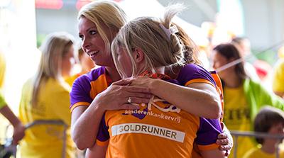 Afbeelding van twee runners met prachting Goldrunner shirt aan geven elkaar een knuffel bij de finish van Run for KiKa.