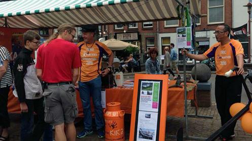 twee deelnemers verkopen in oranje KiKa shirt op de markt voor KiKa