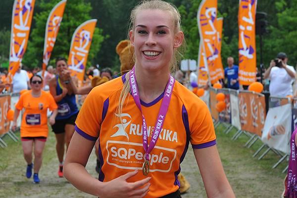 Triathleet van een bedrijventeam komt blij over de finish na de 1/8 triathlon te hebben gedaan voor het goede doel.