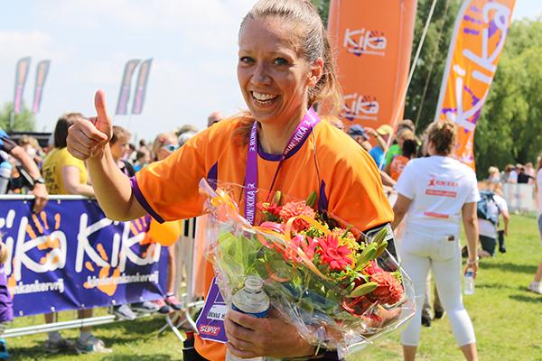 Afbeelding van een hardloper die met bloemen in haar hand en een duim omhoog tevreden aangeeft dat door de goede training en voorbereiding haar Run for KiKa super verlopen is.