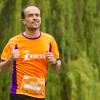 Drie mensen in Run for KiKa shirts vrolijk rennend door een park op een zomerse dag.