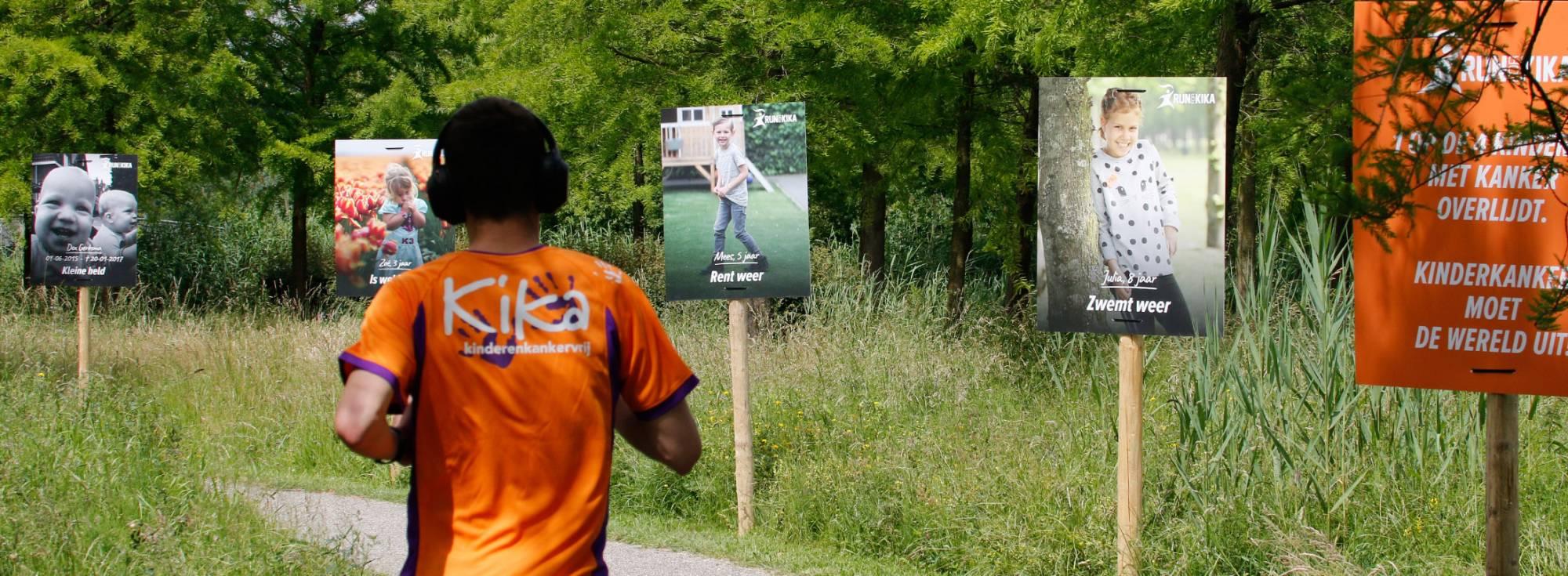 10 km runner komt voorbij de indrukkwekkende borden langs de route van Run for KiKa